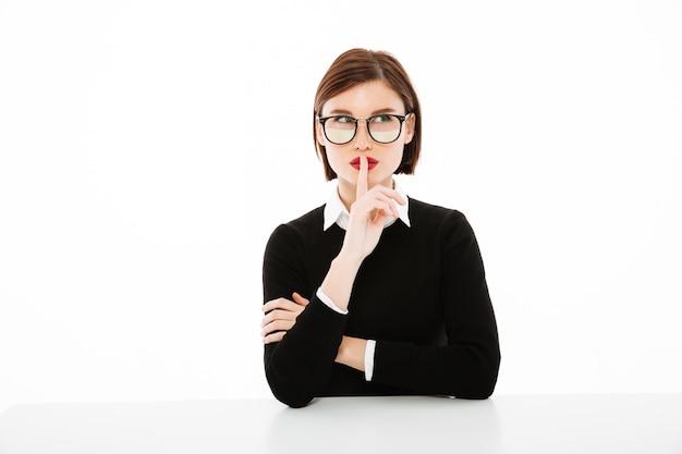 沈黙のジェスチャーを作る若い実業家の肖像画