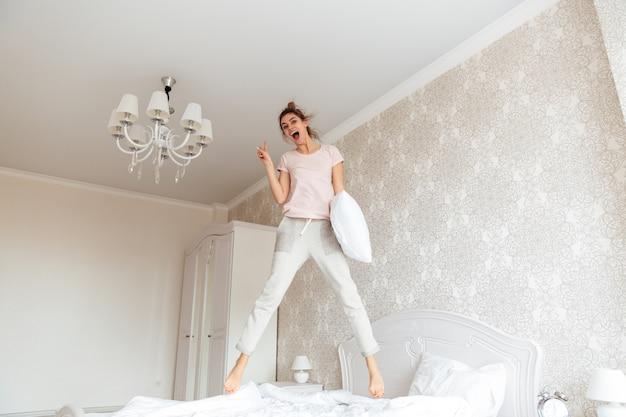 Полная длина образ молодой женщины, развлекаясь на кровати