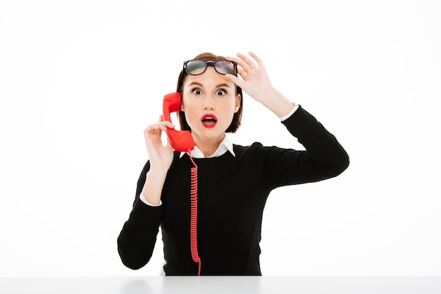 Молодая коммерсантка говоря удивленным телефоном