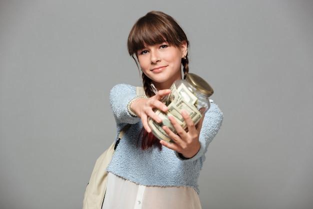 お金でいっぱいの瓶と幸せな女の子