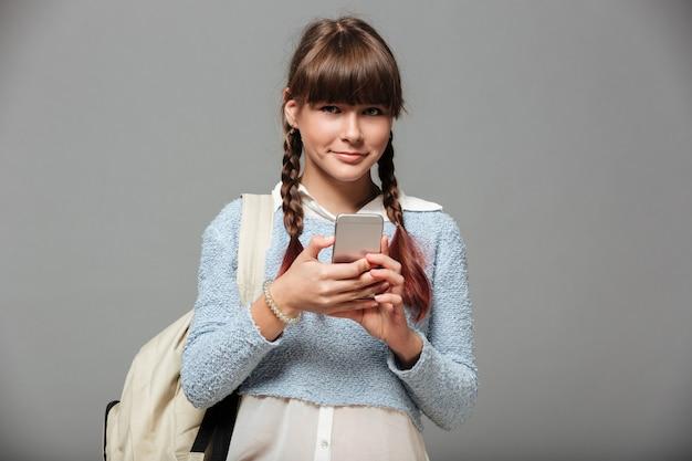 Портрет милой улыбающейся школьницы с рюкзаком