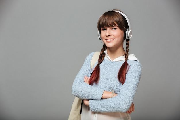 Портрет улыбающейся молодой школьницы с рюкзаком