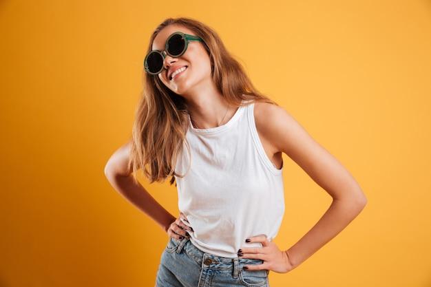 Портрет улыбающейся молодой девушки в солнцезащитных очках