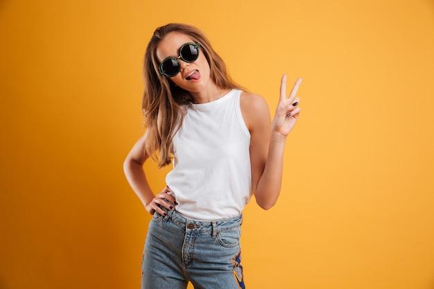 Портрет смешной девушки в солнечных очках показывая жест мира