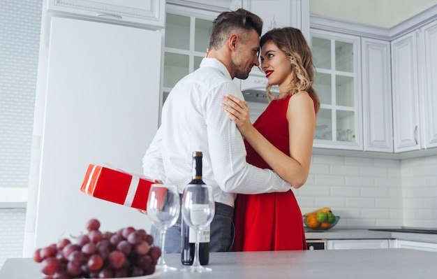 彼は彼女のためのギフトを隠しながら彼女の男を抱いて笑顔の楽しい女性