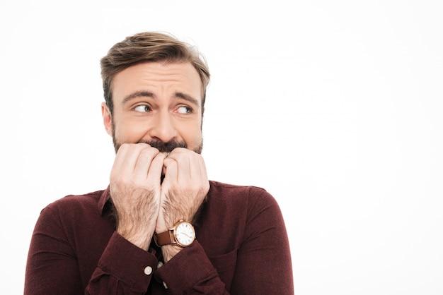 Крупным планом портрет испуганного молодого бородатого мужчины
