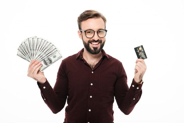 幸せな思考の若い男がお金とクレジットカードを保持しています。