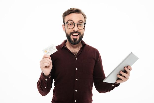 タブレットコンピューターを保持している興奮して幸せな男の肖像
