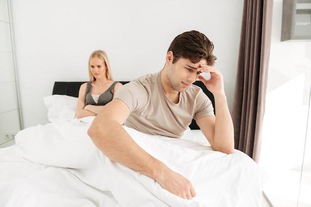 自宅のベッドで彼の悲しい女性と座っている動揺の男