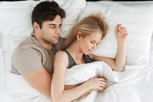 ベッドで寝ている穏やかなハンサムなカップルの肖像画