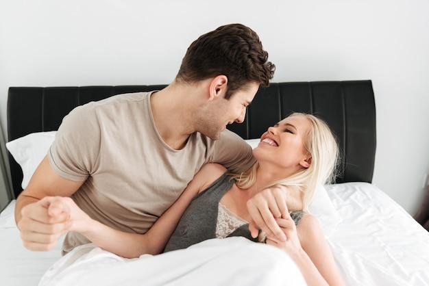 幸せな男と女のベッドで横になっているとハグ