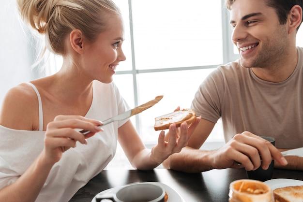 きれいなカップルがキッチンで朝食をとる