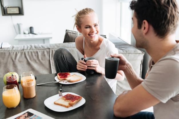 Притягательная жизнерадостная дама смотрит на своего мужчину пока они завтракают