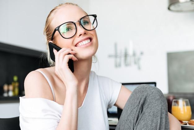 笑みを浮かべて、キッチンでスマートフォンで話しているメガネの陽気な女性