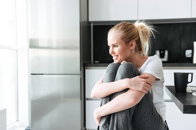 キッチンに座っている間よそ見笑顔のかわいい女性