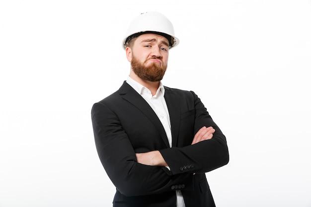 Прохладный бородатый деловой человек в защитном шлеме, держа скрещенные руки