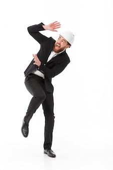 保護用のヘルメットで怖がっているビジネスマンの完全な長さの画像