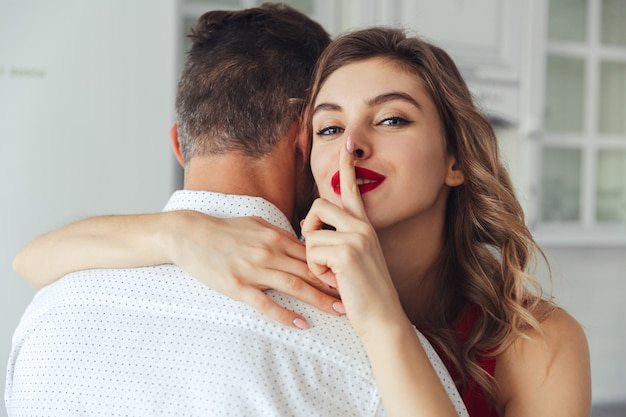 彼女の夫を抱きしめながら沈黙ジェスチャーを作る若い女性