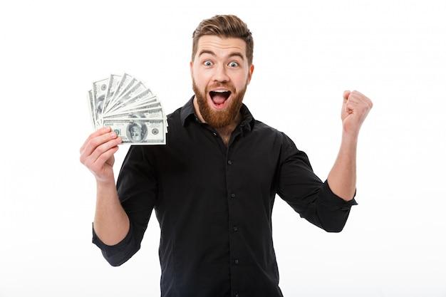 お金を保持しているシャツの陽気なひげを生やしたビジネス男