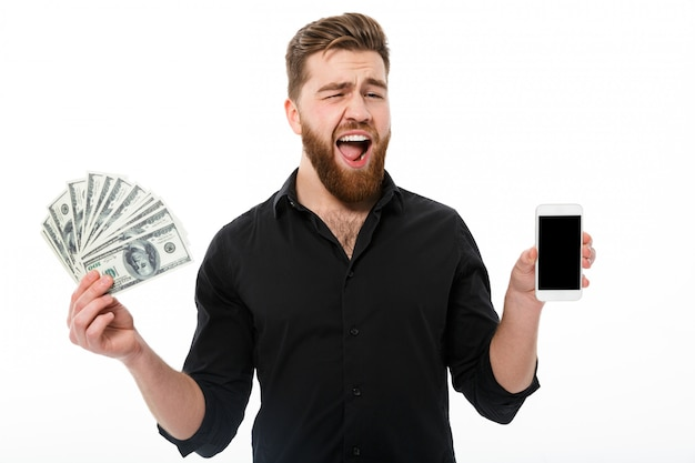 お金を保持しているシャツで幸せなひげを生やしたビジネス男