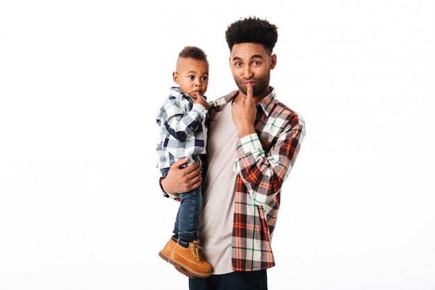 彼の幼い息子を保持している幸せな若いアフリカ人の肖像画