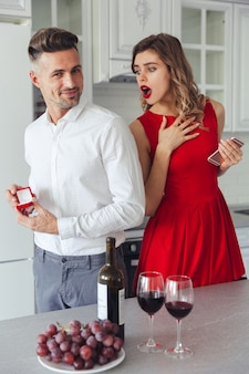 彼のショックを受けたガールフレンドに提案している陽気な男の肖像