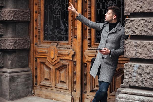 携帯電話を使用して古い建物の近くに立って、指を上げてタクシーを捕まえる深刻なハンサムな男