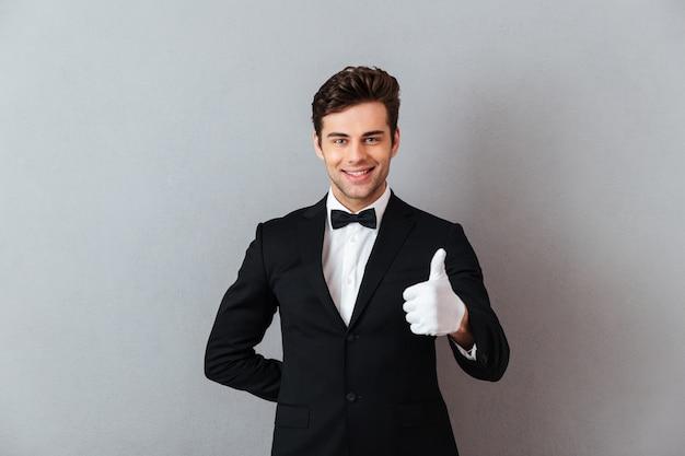 親指を現して孤立した立っている陽気な若いウェイター。