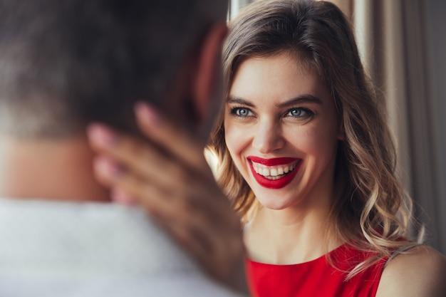 笑う女性の肖像画は彼女の夫を自宅で抱擁します。