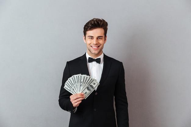 お金を保持している公式のスーツで陽気な若い男。