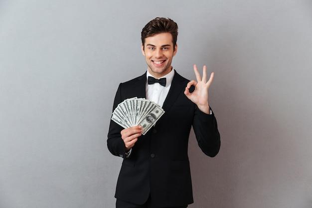 お金を保持している幸せな若い男。