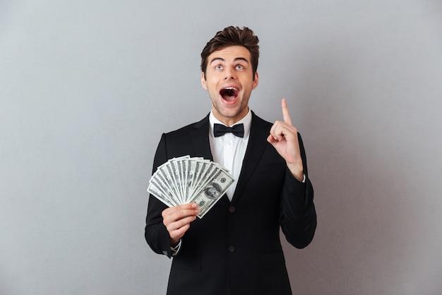 指しているお金を保持している公式のスーツで叫んでいる男。