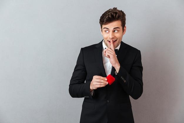 プロポーザルリングとボックスを保持している公式のスーツで笑みを浮かべて男