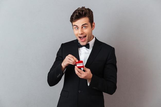 Возбужденный мужчина в официальном костюме держит коробку с предложением кольцо.