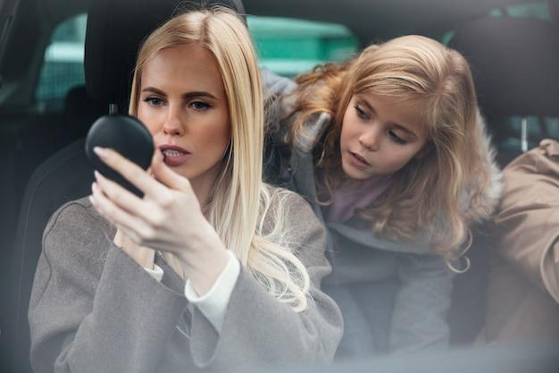 Женщина делает макияж взгляд на зеркало