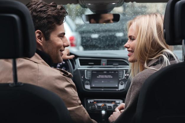 Счастливые молодые влюбленные в машине, глядя друг на друга.