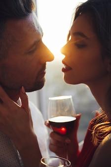 日没で彼女の男にキスワインのグラスを持つ若い女