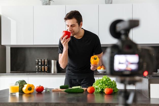 彼のビデオブログエピソードを撮影する魅力的な若い男