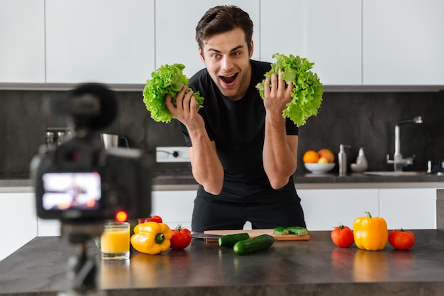 彼のビデオブログエピソードを撮影する幸せな若い男