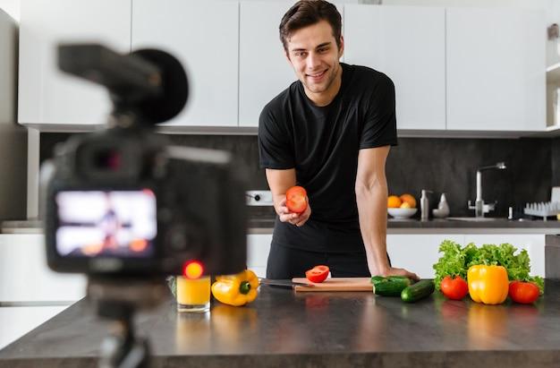 彼のビデオブログエピソードを撮影する若い男の笑みを浮かべてください。