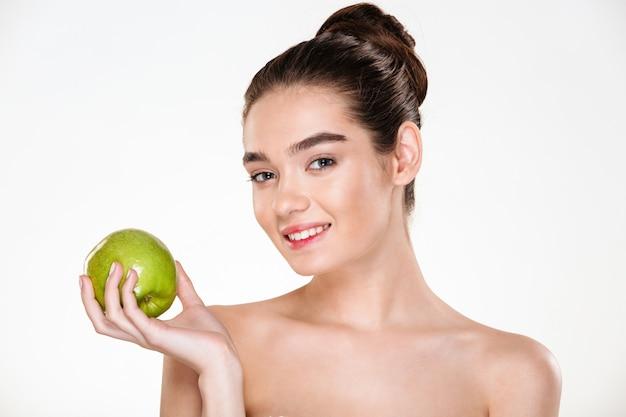 彼女の手のひらに青リンゴを押しながら見ている柔らかい肌とかなり笑顔の女性の美しさの肖像画