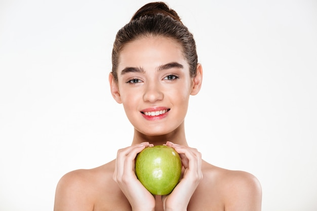 Великолепная женщина с каштановыми волосами в булочке держит большое зеленое яблоко в обеих руках, как в форме сердца