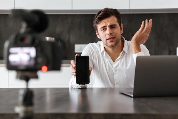 彼のビデオブログエピソードを撮影するハンサムな若い男