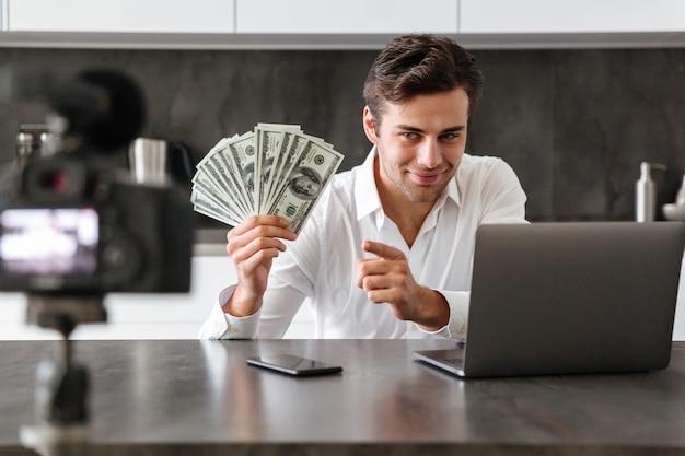Улыбающийся молодой человек снимает свой видео-блог о новых технических устройствах, сидя за кухонным столом с ноутбуком и показывая кучу денежных банкнот