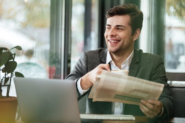 コーヒーを飲みながらよそ見しながらラップトップコンピューターと新聞とカフェのテーブルに座って幸せなビジネスマン