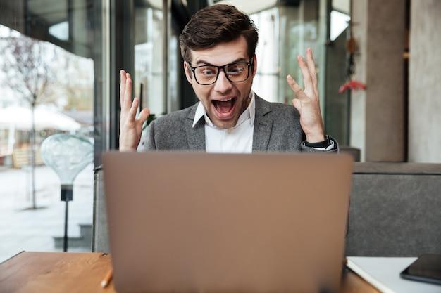 Потрясенный кричащий бизнесмен в очках сидит за столом в кафе и радуется, глядя на ноутбук