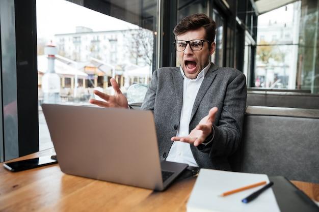 カフェでテーブルのそばに座ってラップトップコンピューターを見ながら眼鏡の怒っているショックを受けたビジネスマン