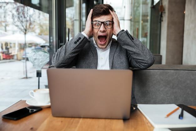 Взволнованный кричащий бизнесмен в очках сидит за столом в кафе и держит голову