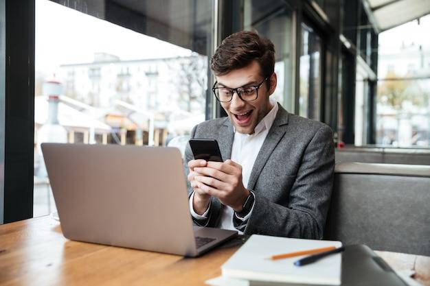 ラップトップコンピューターとカフェのテーブルのそばに座って、スマートフォンを使用して眼鏡で驚いて幸せなビジネスマン