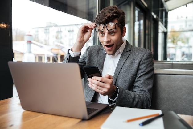 Удивленный бизнесмен в очках, сидя за столом в кафе, держа смартфон и глядя на портативный компьютер